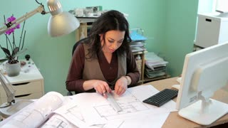 Architect woman working on a new project in her office. Blusiness woman with blueprints on the table