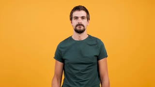 Attractive man slaps himself a couple of times on yellow orange background. Silly funny person