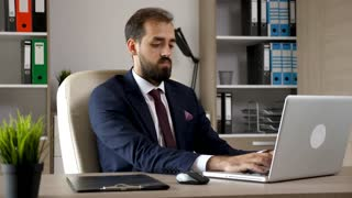 Attractive young businessman in the office types on the computer then looks in a folder with charts. Successful working entrepreneur in online banking