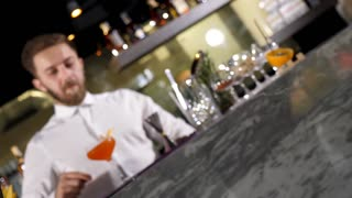 Bartender placing a glass with fresh made cocktail in front of the bar table. Spin zoom in footage
