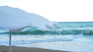 Beach umbrella blowing in the wind near the sea