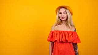 Beautiful gorgeous bored blonde woman isolated on orange yellow background. Slow motion footage