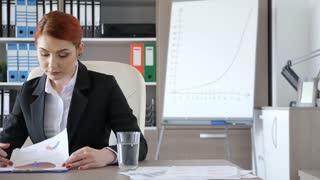 Beautiful redhead businesswoman at her desk in the office looking through paperwork. Corporate lifestyle