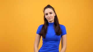 Beautiful woman in blue t-shirt being bored on vivid orange background in studio. Arrogant girl
