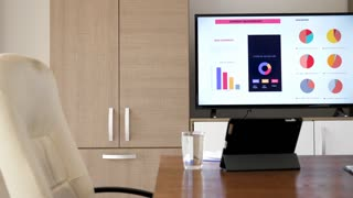 Big screen plasma TV that displays company sales report in empty conference room before the meeting starts. Dolly close up footage