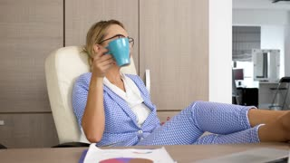 Blonde successful businesswoman relaxing at office desk with her feet up on the table. Relaxation after a long day of work. She is drinking coffee. Dolly slide footage