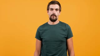 Bored man wearing a casual green t-shirt and chewing gum on yellow orange background