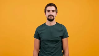 Bored puzzled man slaps himself a couple of times with both hands on yellow orange background