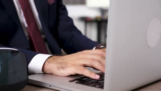 Businesman hands typing on laptop keyboard in close up. Dolly slide 4K footage