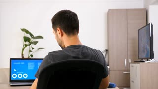 Businessman at home in casual clothes looking on computer screen with animated data chart analysis. Back view. Dolly slider 4K footage