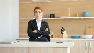 Businesswoman in formal suit home at the kitchen smiling to the camera. Slow motion footage