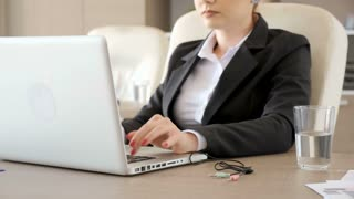 Businesswoman in suits plugging the audio and microphone cords in the laptop while typing