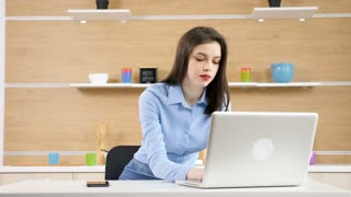 Businesswoman takes her work at home. She is typing on the laptop in the kitchen. At the end of the clip the young lady is smiling to the camera. Static 4K footage