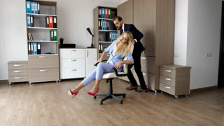 Chair race in the office. Happy smiling businessman is pushing his colleague through the office. Slow motion footage.