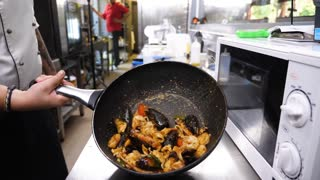 Chef presenting a pan with cooked seafood in resturant kitchen