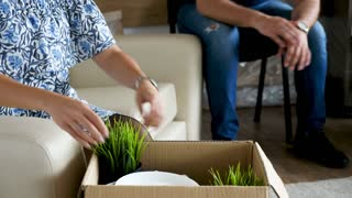 Close up couple unpacking plates and plants in their new house from cardboard boxes