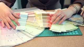 Close up of architect woman choosing colors from color pallet at her desk. Blusiness woman at her work office