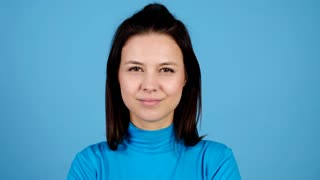 Close up of beautiful woman smiling at the camera on blue background. Attractive happy girl portrait. Slow motion footage