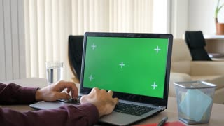Close up of man working on the computer with a green screen mock up. He is in a house at day. Dolly slider 4K parallax footage