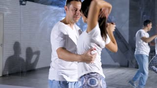 Close up of sexy and beautiful dancers dancing in big empty room. Sport and healthy lifestyle