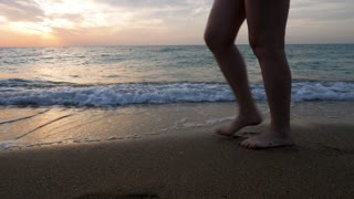Close up woman feet walking on the beach in the water at the sunrise. Relax and calm. Travel and vacation