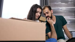 Close up young couple in their new house shopping online for furniture. They are surrounded by cardboard boxes