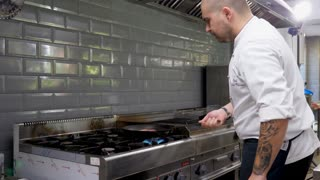 Cook in restaurant kitchen frying meat on stove on a pan. Food and service industry