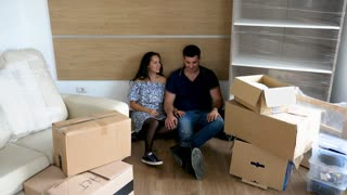 Couple in their new house lying in the floor surrounded by cardboard boxes because they just moved in. New beginnings