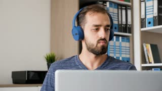 Creative bearded man listens to music while working in his office