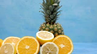 Delicious and healthy exotic fruits on blue background. Close up dolly footage. Lemons, oranges and pineapple