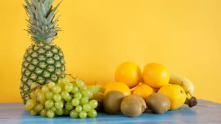Delicious and healthy variety mix of exotic fruits on yellow background. Tropical freshness and summer diet concept