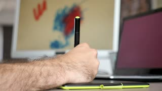 Digital artist graphic designer working on his digital tablet drawing in his office. Close up of the hand while working