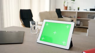 Digital tablet PC with chroma green screen mock up lying on the table in the house. Close up dolly slider 4K footage with parallax effect