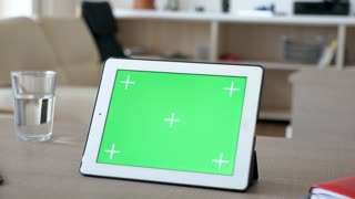 Digital tablet PC with green screen chroma mock-up on a table in house living room. Dolly slider 4K footage with parallax effect