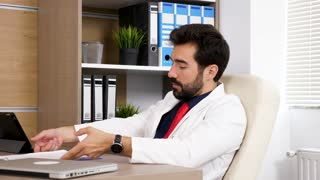 Doctor in his office sitting on the chair at his desk talks to a colleague who we do not see