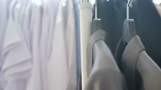 Dolly footage of business suits and shirts on a hanger in close up over a window. Sun rays are getting through the clothes