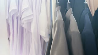 Dolly footage of hanger with business clothes next to a window in a store. Close up shot. The sun rays is getting through the window