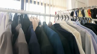 Dolly footage of hangers full with different clothes in a store next to a window. The sun rays are getting through the business suits and other clothes