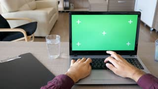 Dolly slider footage of male hands typing on the laptop keyboard with chroma green screen mock up in his house. POV footage of person typing