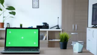 Dolly slider footage of modern laptop with isolated green screen. There is a man walking in the backgorund of the living room and sits on the couch looking at the TV