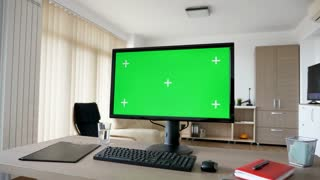 Dolly slider footage Personal PC computer with big green screen chroma mock up on the table in the living room. A guy is entering the room in background while the TV is on and sits on the sofa looking