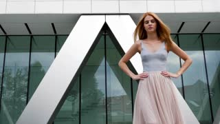 Fashionable glamour redhead model posing at the camera. Slow motion footage