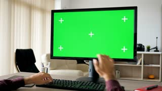 First person view - man hands typing on computer keyboard with big green screen chroma mock-up. The PC is on the desk in living room and the TV is on in the background. Dolly slider 4K footage with