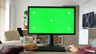 First person view - man hands typing on computer keyboard with big green screen chroma mock-up. The PC is on the desk in living room and the TV is on in the background