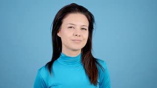 Girl shakes her hair all arround her head on blue background. Slow motion footage