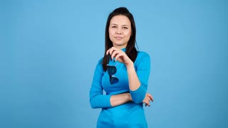 Glamour bored woman playing with her sunglasses on blue background. Pretty fashionable woman posing in studio. Slow motion 4K footage of attractive young brunette