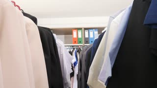 Going through hangers with business and casual clothes in a store. Medium dolly footage