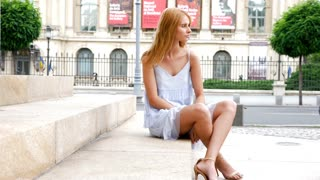Gorgeous beautiful young woman model sitting on the stairs in the city. Slow motion footage