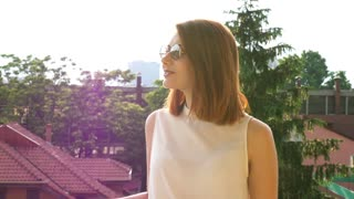 Gorgeous woman in cool glasses on the balcony. Slow motion footage