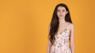 Gorgeous woman in summer outfit smiling shy to the camera isolated on orange yellow background in studio
